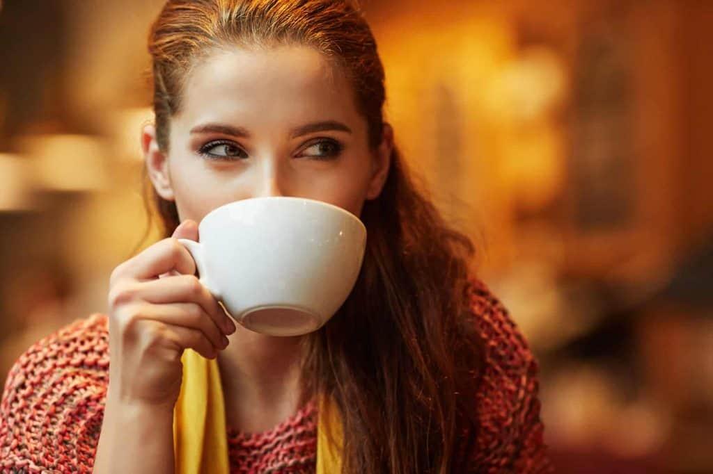 Frau mit Tasse vor dem Mund